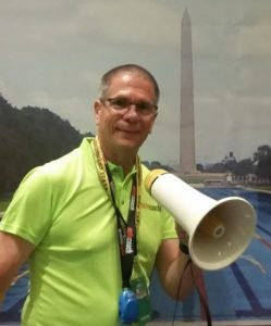 Coach with bullhorn in front of Washington Monument and swim pool.