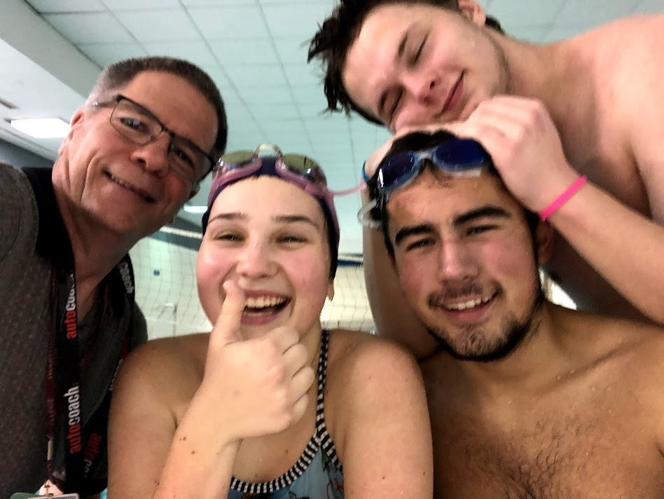 Coach Mark Rauterkus and three of the Sci-Tech swimmers after a 6 am swim practice at the Sci-Tech swim pool.